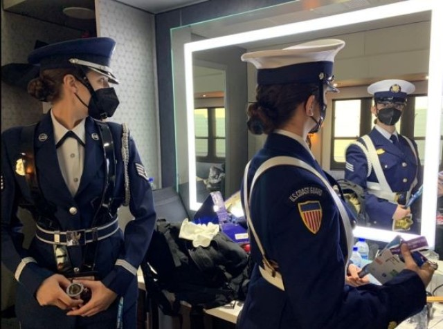 U.S. Air Force Staff Sgt. Hannah Larson, left, and U.S. Coast Guard Seaman Valentina DiZio inspect their uniforms in the secure area of the Raymond James Stadium compound before moving to the stadium for the opening ceremony performance for Super Bowl LV in Tampa, Florida, Feb. 7, 2021. The U.S. Armed Forces Color Guard is comprised of service members from the ceremonial guard units stationed in and around Washington, D.C.