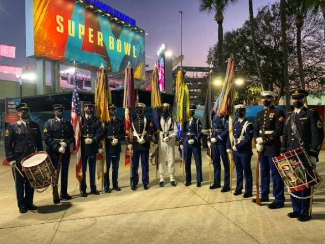 The U.S. Armed Forces color guard stands at the entrance of the Raymond James Stadium just after their performance at Super Bowl LV in Tampa, Florida, Feb. 7, 2021. From left to right, U.S. Army Sgt. 1st Class Derek Stults, U.S. Army Sgt. Christopher WilsonPoston, U.S. Army Sgt. Ryan Weber, U.S. Army Sgt. Collin Gorman, U.S. Marine Sgt. Franklin Taft, U.S. Navy Petty Officer 3rd Class James Hunter, U.S. Air Force Staff Sgt. Hannah Larson, U.S. Air Force Airman 1st Class Zackary Tronnes, U.S. Coast Guard Seaman Valentina DiZio, U.S. Marine Lance Cpl. Hayden Manu, and U.S. Army Sgt. 1st Class Robert Marino. The U.S. Armed Forces Color Guard is comprised of service members from the ceremonial guard units stationed in and around Washington, D.C.