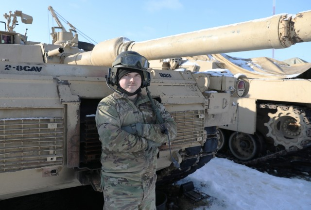 "Cpl. Keaton Williamson, a tanker assigned to Bravo ""Eagar Arms"" Company, 2nd Battalion, 8th Cavalry Regiment, poses with the Abrams tank he operates while deployed to the Pabrade Training Area, Lithuania. Williamson's Family have long served as tankers in the U.S. Army. Since arriving to Lithuania, Williamson recently found out he has a cousin he can add to his Families list of Army tankers. (U.S. Army photo by Sgt. Alexandra Shea)"