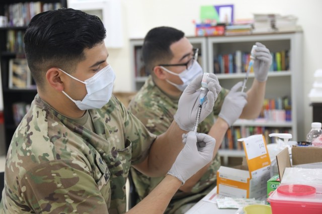 Spc. Michael Meza and Spc. John Cera, healthcare specialists with the 228th Combat Support Hospital, draw doses of the Moderna COVID-19 vaccine from vials at Camp Arifjan, Kuwait, Jan. 18, 2021. Camp Arifjan is utilizing a phased distribution of the vaccine, as specified by the Department of Defense, beginning with medical personnel and first responders. (U.S. Army photo by Sgt. 1st Class Noel Gerig, 1st TSC Public Affairs)
