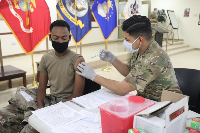 Spc. Michael Meza, healthcare specialist, 228th Combat Support Hospital, administers the Moderna COVID-19 vaccine to Spc. Sarrod Hearn, radiology specialist, 228th Combat Support Hospital, at Camp Arifjan, Kuwait, Jan. 18, 2021. Camp Arifjan is utilizing a phased distribution of the vaccine, as specified by the Department of Defense, beginning with medical personnel and first responders. (U.S. Army photo by Sgt. 1st Class Noel Gerig, 1st TSC Public Affairs)
