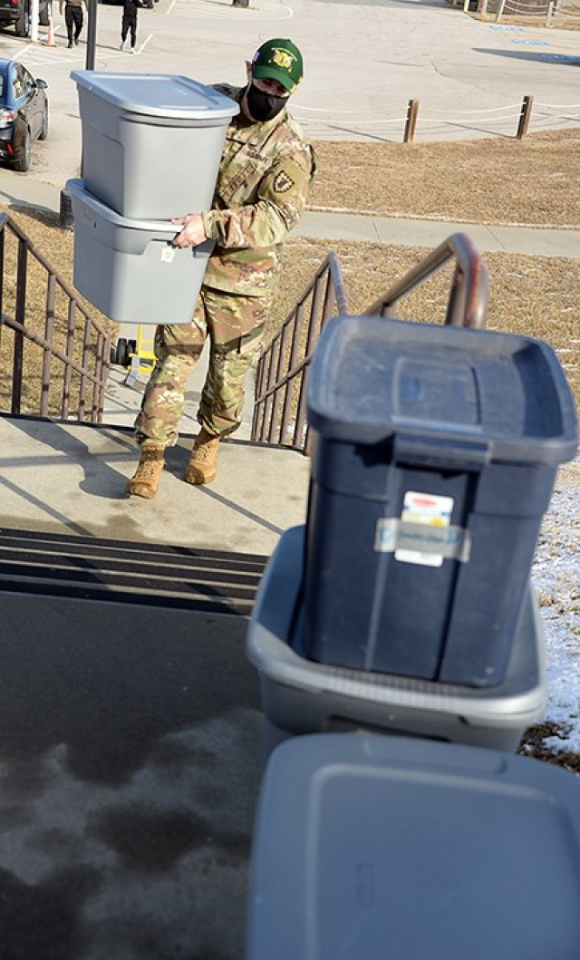 Chaplain (Capt.) Mike Troutt carries bins filled with donated children's clothing from the temporary collection site to what will become the Justice Closet for new parents in the 15th MP Brigade to use Feb. 5 at the 40th Military Police Battalion (Detention) buildings. Photo by Prudence Siebert/Fort Leavenworth Lamp