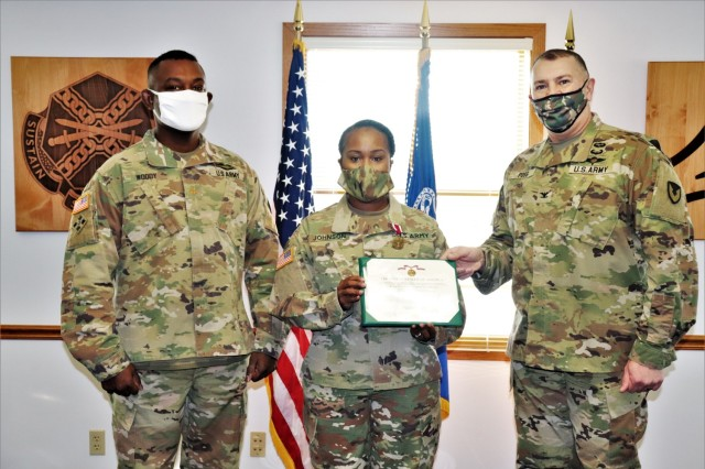 Fort McCoy Garrison Commander Col. Michael D. Poss (right) presents Master Sgt. Cynthia P. Johnson with an Army Meritorious Service Medal on Jan. 22, 2021, at the garrison headquarters building at Fort McCoy, Wis. Johnson earned the medal for meritorious service with Fort McCoy Garrison between 2018 and 2021. Also pictured is Maj. Eddie Woody, Fort McCoy Garrison Headquarters and Headquarters Company commander. (U.S. Army Photo by Scott T. Sturkol, Public Affairs Office, Fort McCoy, Wis.)