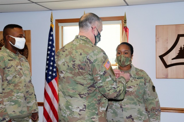 Fort McCoy Garrison Commander Col. Michael D. Poss presents Master Sgt. Cynthia P. Johnson with an Army Meritorious Service Medal on Jan. 22, 2021, at the garrison headquarters building at Fort McCoy, Wis. Johnson earned the medal for meritorious service with Fort McCoy Garrison between 2018 and 2021. (U.S. Army Photo by Scott T. Sturkol, Public Affairs Office, Fort McCoy, Wis.)