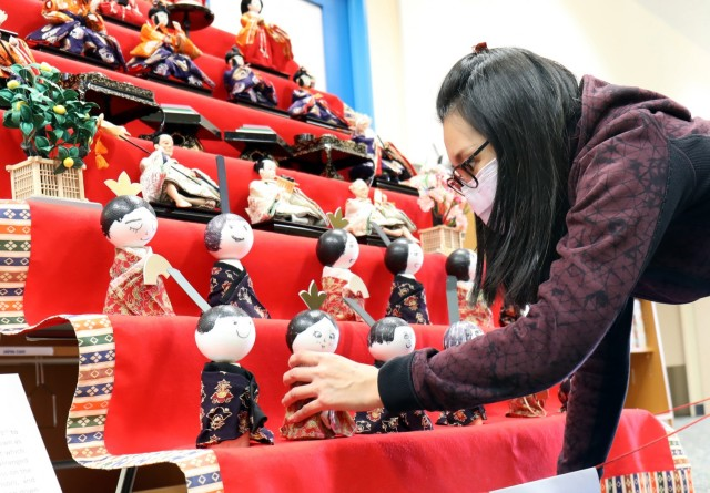 "Sabrina Tsai, manager of the Camp Zama Arts and Crafts Center, arranges Japanese ""Hinamatsuri"" dolls on a display at the Sagamihara Family Housing Area Library, SFHA, Japan, Feb. 11."