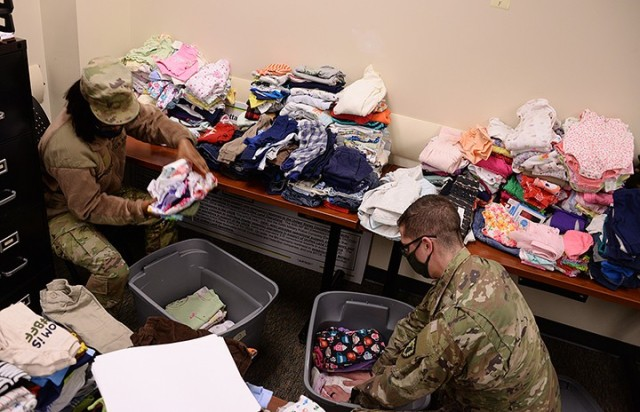 Pvt. Monique Mason, 291st Military Police Company, 40th Military Police Battalion (Detention), and Spc. Joshua Solano, 256th MP Company, 40th, pack pre-sorted children's clothing into bins to transfer the donations from a temporary collection site to what will become the permanent closet in a nearby building Feb. 5 at the 40th MP Battalion Headquarters. Photo by Prudence Siebert/Fort Leavenworth Lamp