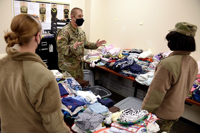 Chaplain (Capt.) Mike Troutt explains to Pvt. Anna Gram and Pvt. Monique Mason, 291st Military Police Company, 40th Military Police Battalion (Detention), how he would like pre-sorted children's clothing packed into bins to transfer the donations from a temporary collection site to what will become the permanent closet in a nearby building Feb. 5 at the 40th MP Battalion Headquarters. Photo by Prudence Siebert/Fort Leavenworth Lamp