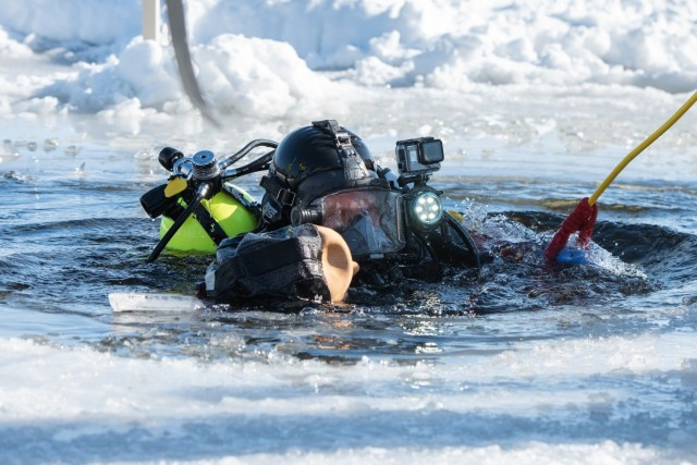 A firefighter with the Directorate of Emergency Services Fire Department dive team completes dive training under ice Feb. 3, 2021, at Big Sandy Lake on South Post at Fort McCoy, Wis. The department conducts surface and dive training with ice-covered lakes on post annually. (U.S. Army Photo by Cedar Wolf, Fort McCoy Multimedia-Visual Information Office)