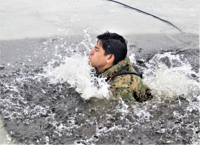 A Fort McCoy Cold-Weather Operations Course (CWOC) Class 21-02 student participates in cold-water immersion training Jan. 15, 2021, at Big Sandy Lake on South Post at Fort McCoy, Wis. CWOC students are trained on a variety of cold-weather subjects, including snowshoe training and skiing as well as how to use ahkio sleds and other gear. Training also focuses on terrain and weather analysis, risk management, cold-weather clothing, developing winter fighting positions in the field, camouflage and concealment, and numerous other areas that are important to know in order to survive and operate in a cold-weather environment. The training is coordinated through the Directorate of Plans, Training, Mobilization and Security at Fort McCoy. (U.S. Army Photo by Scott T. Sturkol, Public Affairs Office, Fort McCoy, Wis.)
