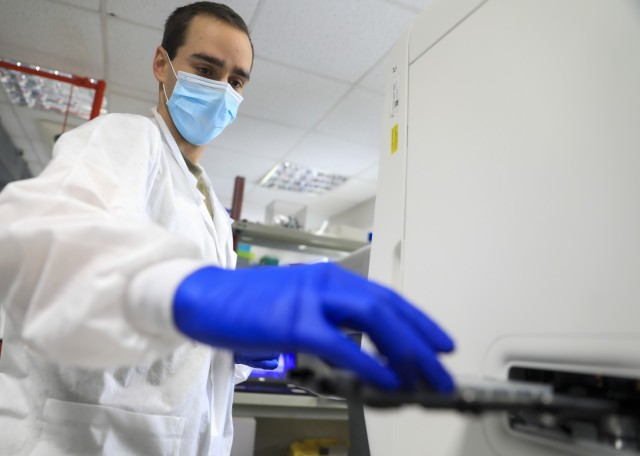 Capt. Cole Anderson, chief, Microbiology, Landstuhl Regional Medical Center, prepares a plate of COVID-19 specimens for testing with a Polymerase Chain Reaction (PCR) analyzer at LRMC's Infectious Disease Laboratory, Feb. 10. Landstuhl Regional Medical Center recently surpassed 100,000 COVID-19 tests since its first test on March 6, 2020.