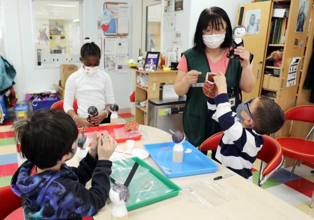 "Marino Nakanowatari, right, a caregiver in the art room at the School Age Center, helps students during a virtual class on how to make Japanese ""Hinamatsuri"" dolls, Sagamihara Family Housing Area, Japan, Feb. 9."