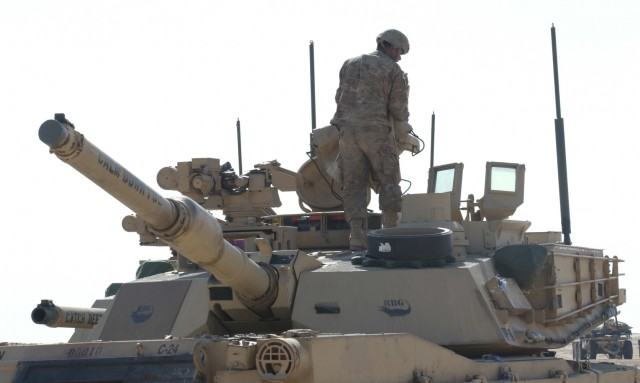 A Soldier from 1st Battalion, 6th Infantry Regiment, 2nd Brigade Combat Team, 1st Armored Division, carries out preventative maintenance checks and services on the top of an M1 Abrams tank, Jan. 29, 2021, to insure it is ready for Iron Union 14 at Al Hamra Training Center in the United Arab Emirates. Iron Union is a recurring, bilateral exercise between Task Force Spartan and the United Arab Emirates Land Forces, designed to strengthen military-to-military relationships through a combined government approach to complex national security challenges. (U.S. Army photo by Staff Sgt. Daryl Bradford, Task Force Spartan Public Affairs)