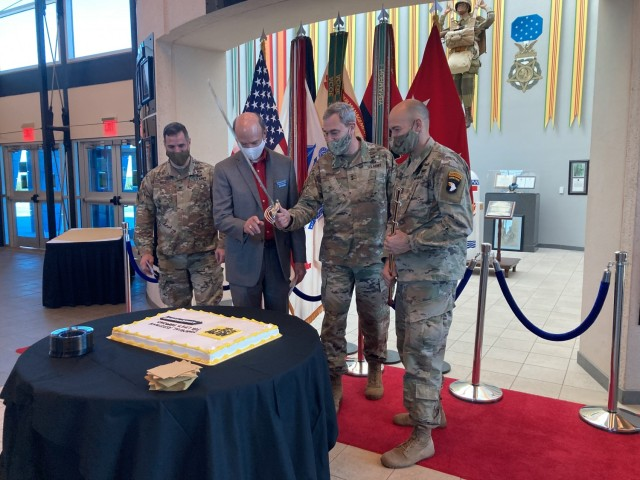 Major General Brian E. Winski, commanding general of the 101st Airborne Division and Fort Campbell, center, prepares to cut a cake Feb. 5 during the Army Emergency Relief campaign kickoff at McAuliffe Hall with Col. Jeremy D. Bell, garrison commander; left, Donald Jenkins, Jenkins and Wynne new car dealerships president; and Command Sgt. Maj. Bryan D. Barker, 101st Abn. Div. senior enlisted adviser.
