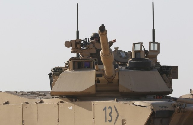 A US Army Soldier from 1st Battalion, 6th Infantry Regiment, directs a neighboring tank to the area the M1 Abrams tank he occupies is moving during a Situational Training Exercise, Jan. 30, 2021, for Iron Union 14 at Al Hamra Military Airfield in United Arab Emirates. Iron Union is a recurring exercise that expands partner capacity and supports security cooperation objectives in the Middle East and Southwest Asia. (U.S. Army photo by Staff Sgt. Daryl Bradford)