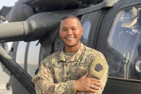 Spc. John Pack, a signal support specialist with 1st Battalion, 137th Aviation Regiment, poses for a photo after performing a radio check on a UH-60 Blackhawk.  Spc. Pack is credited for using Bystander Intervention to set a positive climate for Soldiers assigned to the 28th Expeditionary Combat Aviation Brigade.