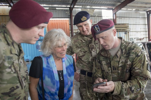 Deputy Chief of Mission for the U.S. Embassy in the Federated States of Micronesia, Joanne Cummings, and Her Majesty's Royal Navy Capt. Peter Olive, Deputy Mission Commander of Pacific Partnership 2018 (PP18), review photos taken on U.S. Army Capt. Daniel Mathews' phone following a humanitarian assistance/disaster relief training exercise conducted by local Yap first responders and supervised by servicemembers supporting PP18, March 28.  (U.S. Navy photo by Mass Communication Specialist 1st Class Byron C.