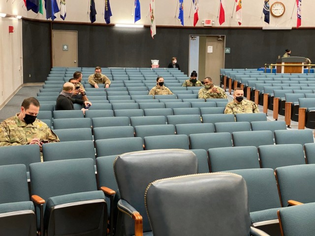 Soldiers and civilians wait after receiving the first dose of the COVID-19 vaccine at the Hunter Auditorium.