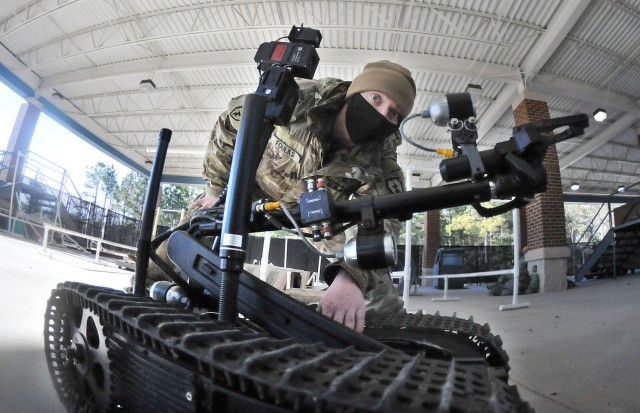 Sgt. Dustin Foulks focuses on the manipulator arm of an explosive ordnance disposal robot during an EOD Specialist Course robotics familiarization Feb. 4 at Rose Hall located on the Ordnance Campus.  During the session, students were required to set up a controller and robot then complete several tasks.