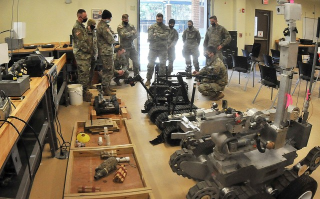 Phase I Explosive Ordnance Disposal Course students listen to Staff Sgt. Daniel Dreibelbis (right, stooping) explain steps in preparing EOD robots for operation during a familiarization class Feb. 4 at Rose Hall. Phase I of the course is seven weeks long. Phase II, held at Eglin Air Force Base, Fla., is seven months in duration.
