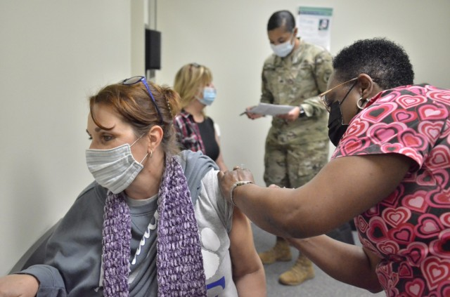 Kesha Ladd, Fort Campbell High School teacher, foreground, receives a COVID-19 vaccination, Feb. 12, from Patsey Simmons, licensed practical nurse, while Kimberly Butts, FCHS guidance counselor, reviews information with Sgt. Tametra Jalomo, medic assigned to Blanchfield Army Community Hospital.