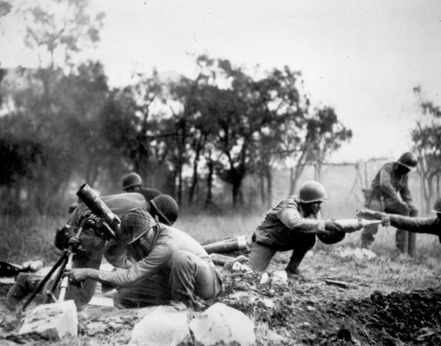 A mortar company of the 92nd Infantry Division passes ammunition and heaves it toward the Germans in an almost endless stream near Massa, Italy. This company is credited with liquidating several machine gun nests in Nov. 1944. (U.S. Army Photo)