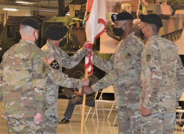 Col. Wheeler R. Manning, brigade commander, 403rd AFSB, passes the brigade colors to Command Sgt. Maj. Christopher J. Reaves, incoming brigade command sergeant major, during the brigade's change of responsibility ceremony at Camp Carroll, South Korea, Feb. 10.