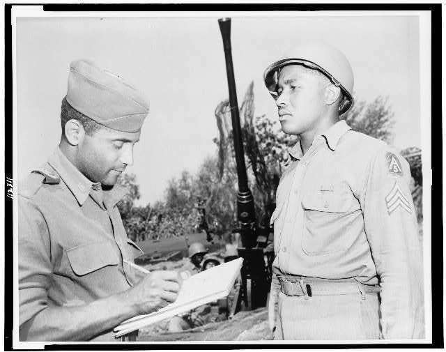 Oliver W. Harrington, a New York City artist correspondent, sketches anti-aircraft section chief, Sgt. Carl K. Hilton of Pine Bluff, Arkansas, who is with the Fifth Army in Italy in1944. (U.S. Army Photo)
