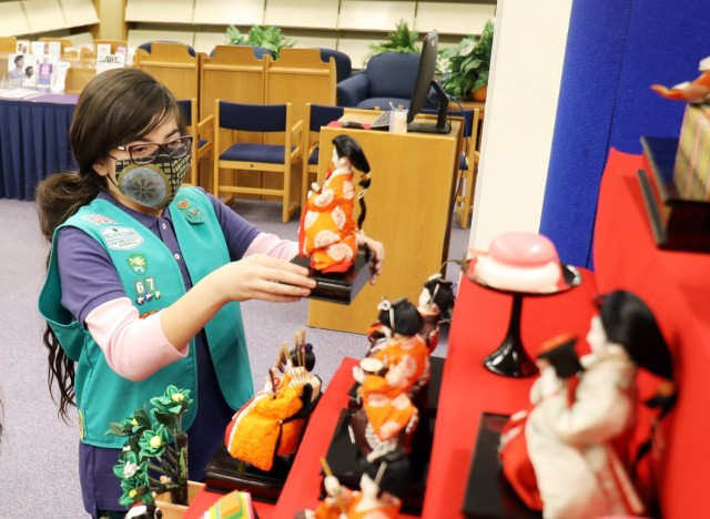 """Lilly de Castro, 10, a member of Junior Girl Scout Troop 67, places a doll on the """"Hinamatsuri"""" display at the Camp Zama Library, Camp Zama, Japan, Feb. 18."""