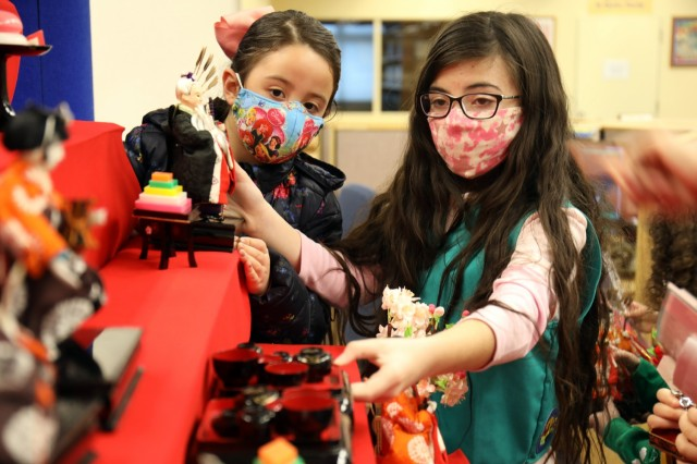 """Sophia Fischer, left, 7, a member of Brownie Troop 21, and Layla de Castro, 10, a member of Junior Girl Scout Troop 67, arrange dolls on the """"Hinamatsuri"""" display at the Camp Zama Library, Camp Zama, Japan, Feb. 18."""