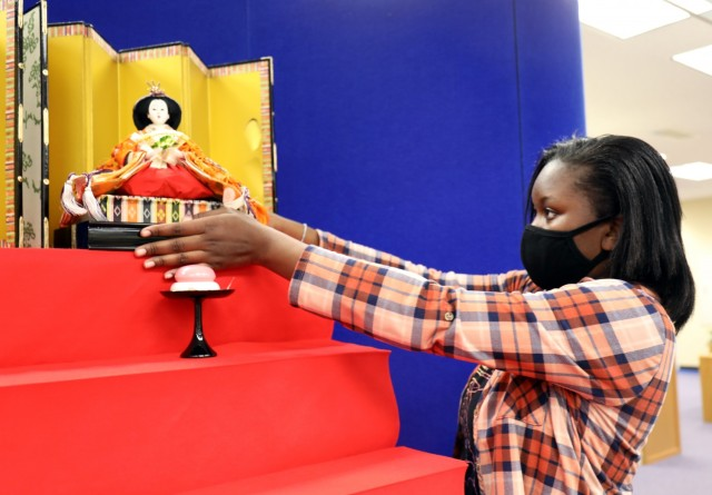 """Madison Swanigan, 13, a member of Girl Scout Troop 600, places the empress doll on the """"Hinamatsuri"""" display at the Camp Zama Library, Camp Zama, Japan, Feb. 18. The display's top tier is reserved for the emperor and empress, and members of their court are on the tiers below."""