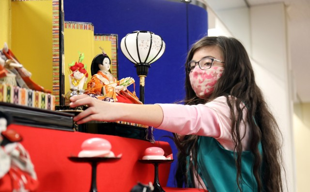 """Layla de Castro, 10, a member of Junior Girl Scout Troop 67, places a doll on the """"Hinamatsuri"""" display at the Camp Zama Library, Camp Zama, Japan, Feb. 18."""