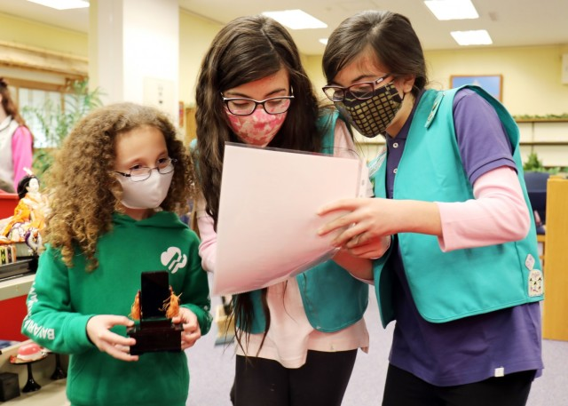 """At center and right, Layla and Lilly de Castro, both 10, and both members of Junior Girl Scout Troop 67, work with Cailyn Nelson, left, 8, a member of Brownie Troop 11, while setting up a """"Hinamatsuri"""" display at the Camp Zama Library, Camp Zama, Japan, Feb. 18."""