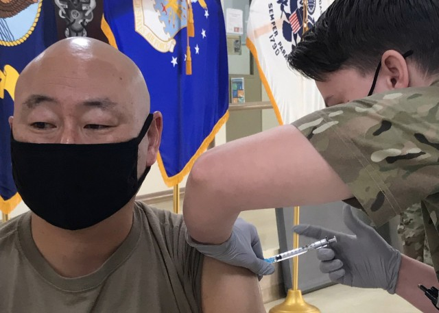 """Lt. Col. Harold Yu, the deputy surgeon for Area Support Group-Kuwait and the officer-in-charge of the U.S. Army Health Clinic Kuwait, looks away as he receives his second Moderna COVID-19 vaccine dose Feb. 15, 2021 at the Camp Arifjan, Kuwait hospital. Yu said: """"This vaccination is no different from any other shot I ever got. Really, I didn't even feel it."""""""