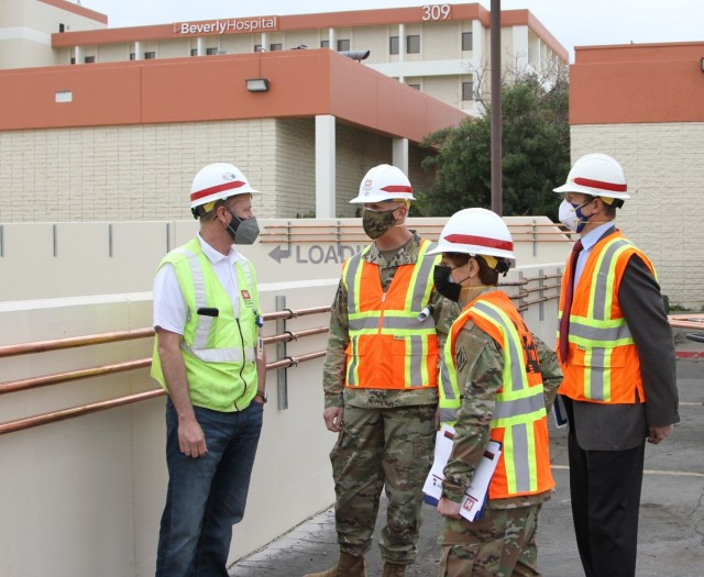 Martin Reed, contracting officer's representative with the U.S. Army Corps of Engineers Rapid Response Technical Center of Expertise at the Omaha District, left, provides project updates to Brig. Gen. Paul Owen, U.S. Army Corps of Engineers South Pacific Division commander, center, during Owen's Feb. 9, 2021 visit to Beverly Community Hospital in Montebello, California. Accompanying Owen were Col. Julie Balten, Los Angeles District commander, second from right, and David Van Dorpe, LA District deputy engineer.