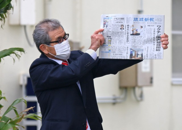 Tsutomu Nakasone, an Okinawa Area Office project manager with the Project Management Branch and 25+ year U.S. Army Corps of Engineers Employee, holds aloft a local Okinawan newspaper that he will place in the USACE 75th Anniversary time capsule. The paper will next be seen when the time capsule is re-opened in 2046 in celebration of USACE being in Japan 100 years. USACE photo by Honey Nixon
