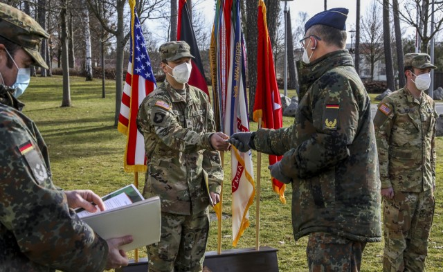 Brig. Gen. Thomas Hambach, Commander Landeskommando Bayern, presents Sgt. Patrick Carter, assigned to Bravo Company, 6th General Support Aviation Battalion, 101st Combat Aviation Brigade, with the Commanders Golden Coin, during an awards ceremony recognizing Carter's air crew for their efforts, Grafenwoehr, Germany, Feb. 18, 2021. Brig. Gen. Christopher Norrie, Commander, 7th Army Training Command, and Brig. Gen. Thomas Hambach, were both present at the award ceremony to thank the crew for their heroic actions.