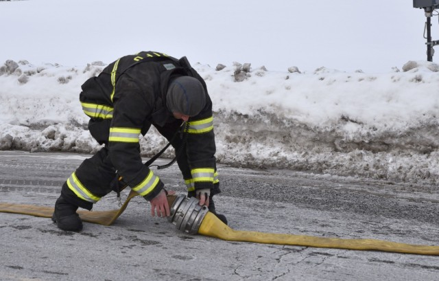 A Rock Island firefighter connects a hose in order to quickly gain access to the fire hydrant system to fight the blaze in a residence's attic.