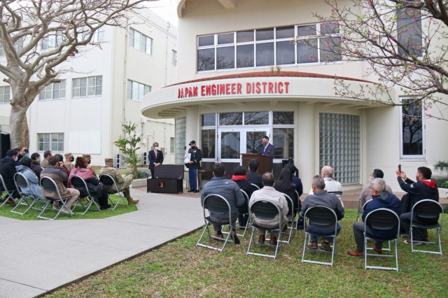A crowd watches as Col. Thomas J. Verell, Jr., Japan Engineer District Commander, and Tsutomu Nakasone, an Okinawa Area Office project manager with the Project Management Branch, place items into a time capsule that will remain sealed until the year 2046. This was part of the 75th Anniversary Celebration of the U.S. Army Corps of Engineers in Japan. The celebration also included speeches, awards, and a cake cutting. USACE photo by Honey Nixon