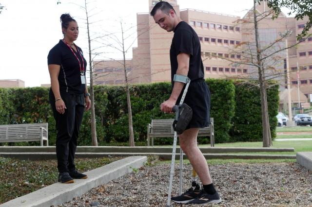 Candace Pellock, physical therapy assistant, guides Army Spc. Ezra Maes at the Center for the Intrepid, Brooke Army Medical Center's rehabilitation center at Joint Base San Antonio-Fort Sam Houston, Texas, Oct. 2, 2019.