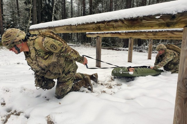 Army Sgt. Michael Metcalf and Spc. Walter Galdamez evacuate a simulated injured soldier in Germany, Jan. 21, 2021, as part of training for a competition.