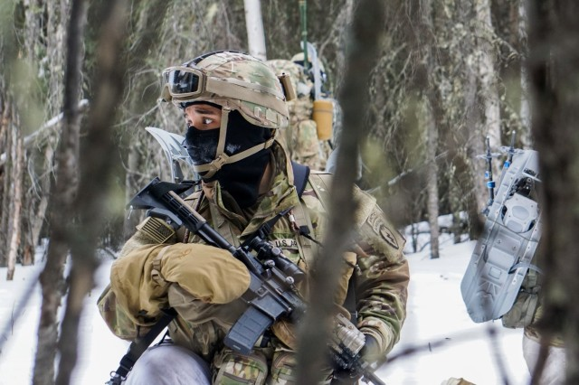 """Sgt. Luis Hernandez, Charlie Company, 3rd Battalion, 509th Parachute Infantry Regiment, 4th Infantry Brigade Combat Team (Airborne), 25th Infantry Division, """"Spartan Brigade,"""" pulls security during a tactical halt while conducting an offensive operation to capture a high value target during exercise Arctic Warrior 21, Feb. 11, 2021, at Donnelly Training Area, Alaska. The Spartan Brigade is the only airborne infantry brigade combat team in the Arctic and Pacific theaters, providing the combatant commander with the unique capability to project an expeditionary force by air."""