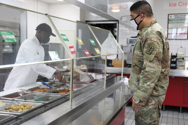 Staff Sgt. Ricardo Morales, right, assigned to the 311th Military Intelligence Battalion, orders lunch Jan. 26 at the dining facility at Camp Zama, Japan. Serving him is a member of the 35th Combat Sustainment Support Battalion's field feeding platoon. When services at the dining facility were interrupted Jan. 21, the field feeding platoon took over operations and began providing hot, takeout-only meals to customers three times a day, seven days a week.