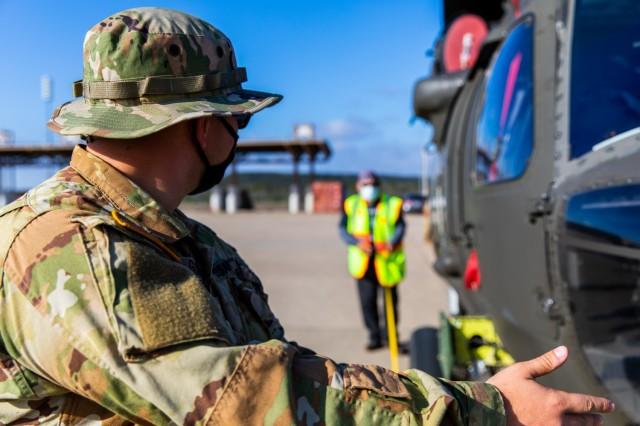 Spc. Mika Garcia, a UH-60 Helicopter Repairer from 3rd Battalion, 227th Aviation Regiment, 1st Air Cavalry Brigade, 1st Cavalry Division, helps Cruz Baca, a Transportation Assistant, in finding the center of balance for the UH-60 Black Hawk at Fort Hood, Texas, February 24, 2021. (U.S. Army Photo by Spc. Froylan Grimaldo)