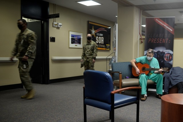 Maj. Douglas Westbrook, a nurse anesthetist at General Leonard Wood Army Community Hospital, plays his guitar in the hospital lobby for customers while off duty. Westbrook said his singing is for people who need calm while in a stressful place in their lives.