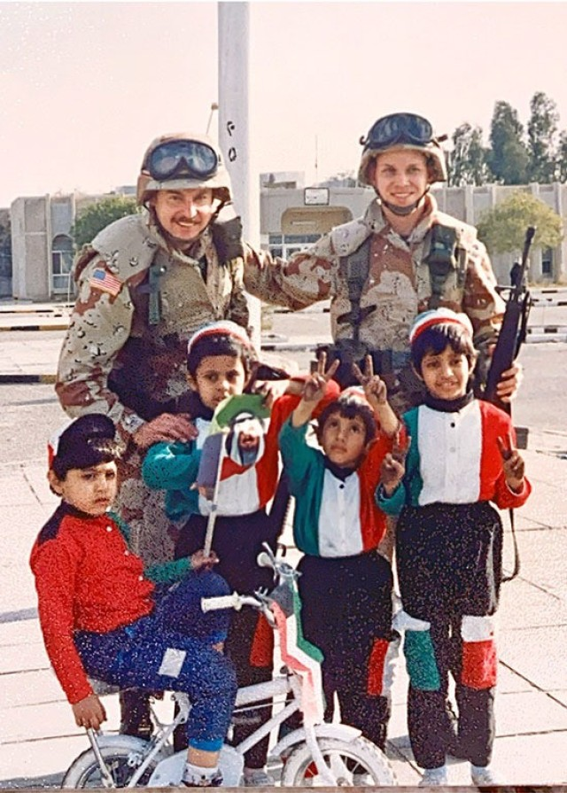 Then-1st Lt. Doug Faith (left) and another Soldier from his Army Reserve unit pose with Kuwaiti children while deployed in support of Operation Desert Storm in 1991. He is now a U.S. Army Aviation and Missile Command attorney adviser. (Courtesy photo)