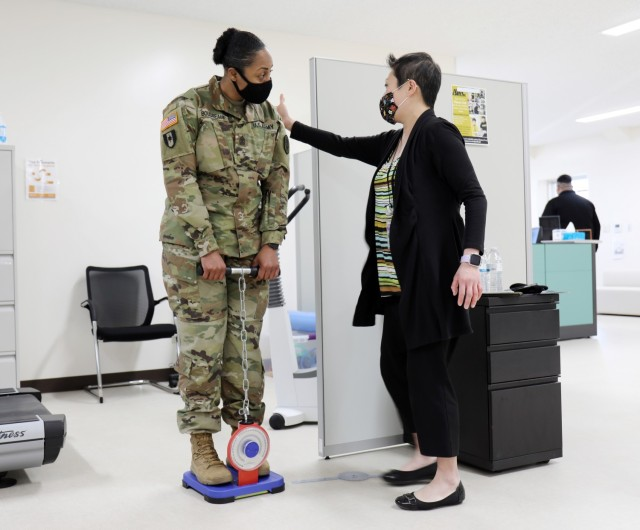 Shannon Vo, right, director of the Camp Zama Army Wellness Center, shows U.S. Army Medical Department Activity – Japan Command Sgt. Maj. Tanya Boudreaux, how to hold her back for the center's back-strength test at the Camp Zama AWC in Bldg. 379, Camp Zama, Japan, Feb. 25.