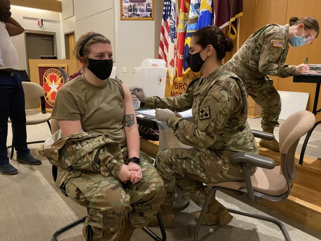 Dr. Nadia Pearson, U.S. Army Medical Center of Excellence Command Surgeon administers the COVID-19 vaccine on February 1, 2021 at Brooke Army Medical Center (BAMC) on Joint Base San Antonio-Fort Sam Houston, Texas to Senior Airman Baylie Higgins, a medical technician who works on BAMC's COVID-19 ward.