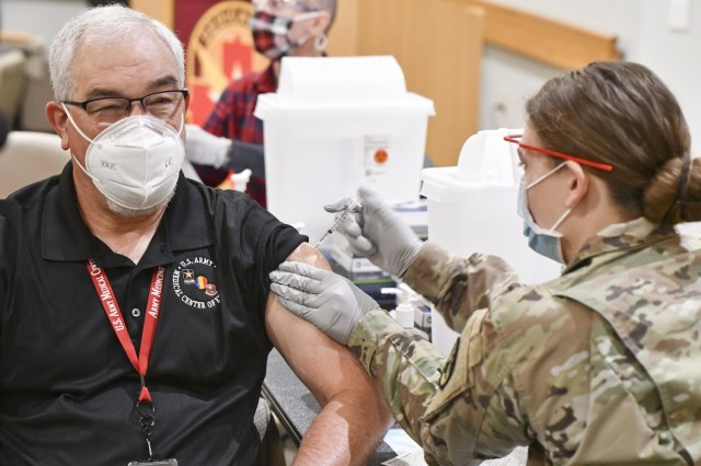 Mr. J.M. Harmon III, U.S. Army Medical Center of Excellence Deputy to the Commanding General is administered the COVID-19 vaccine by Spc. Carley Despain at Brooke Army Medical Center on Joint Base San Antonio-Fort Sam Houston, Texas on February 1, 2021.