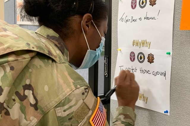 Capt. Lauren Dodd writes her reason to get the COVID-19 vaccination on a wall at the Ft. Knox vaccination site after receiving dose one of the Moderna vaccine.