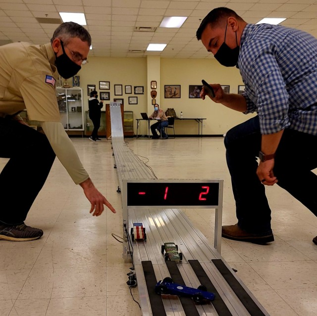 Col. Terry Brannan, Fort Hood Pack 221 Tiger Den Leader and Assistant Chief of staff Personnel Officer for III Corps, and Capt. Jimmy Naranjo, Cub Master and Bears Den Leader with 11th Military Police Battalion check cars at the finish line during the Pinewood Derby held at Fort Hood on February 27. The event was aired virtually for scouts and their families to view. (U.S. Army photo by Maj. Marion Jo Nederhoed)